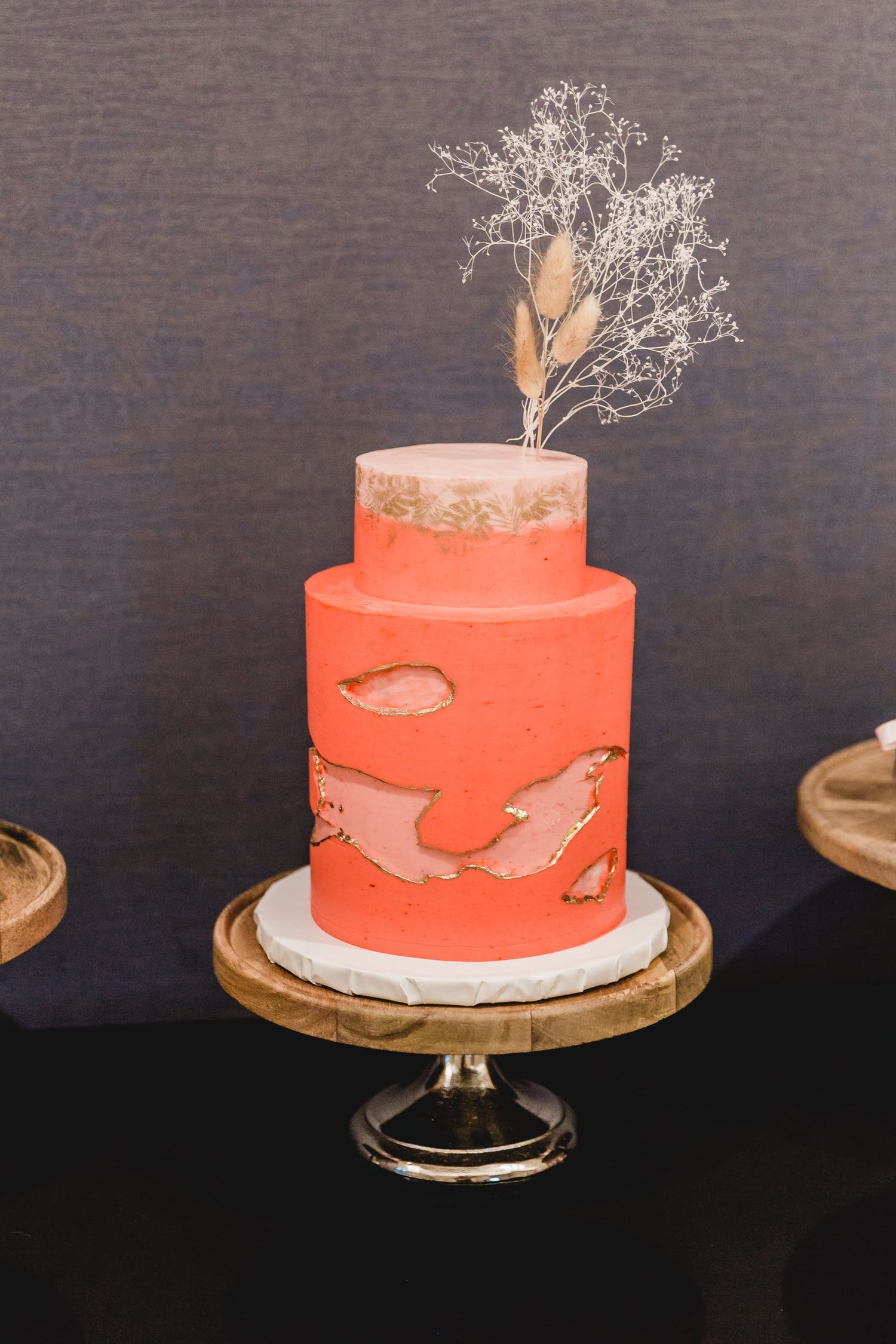 Two tier salmon-colored wedding cake with unique design | PartySlate