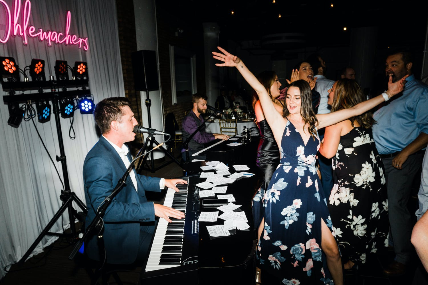 Wedding guest dances next to dueling pianos at wedding reception   PartySlate
