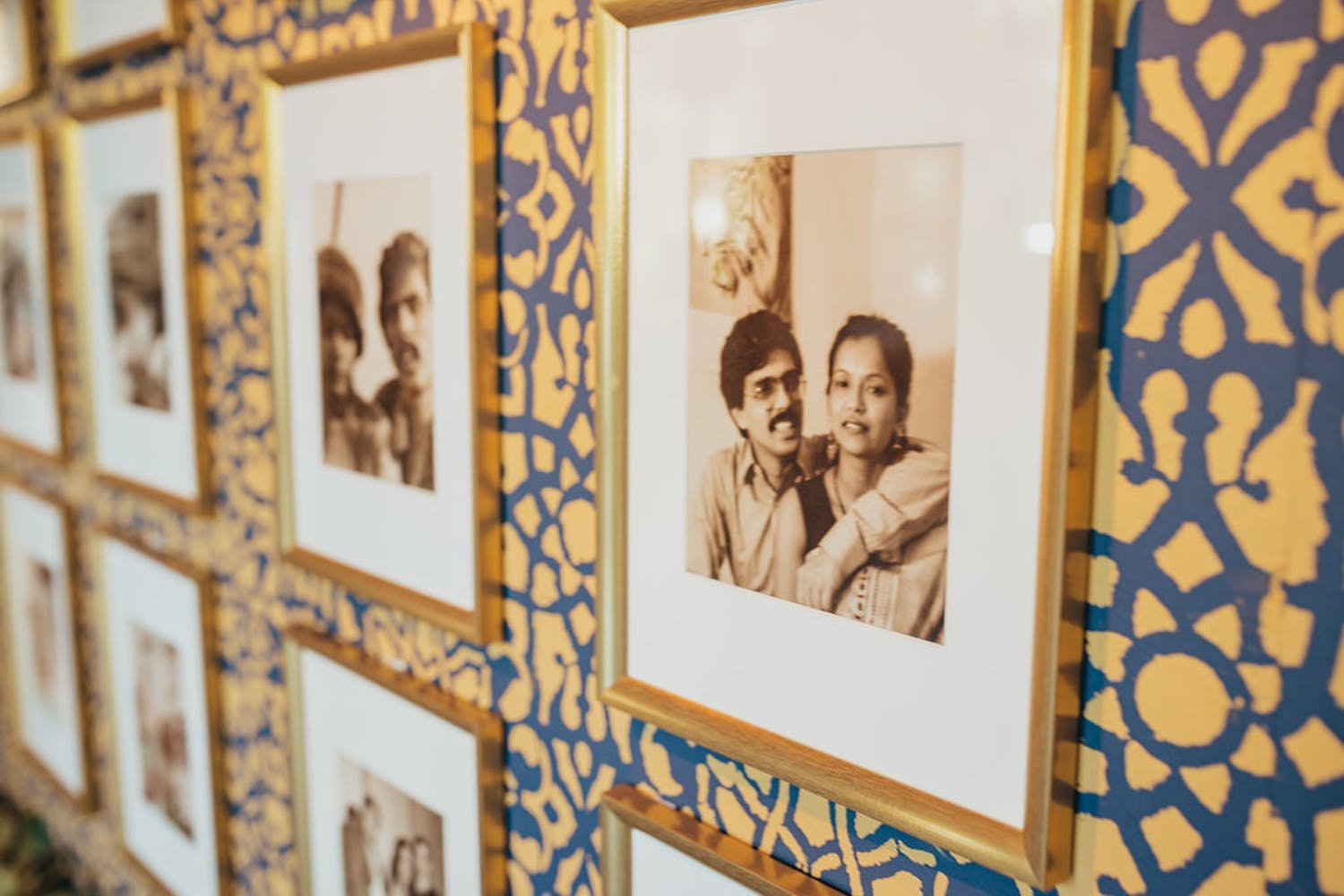 Wall of photos of couple at jewel-toned wedding anniversary party | PartySlate