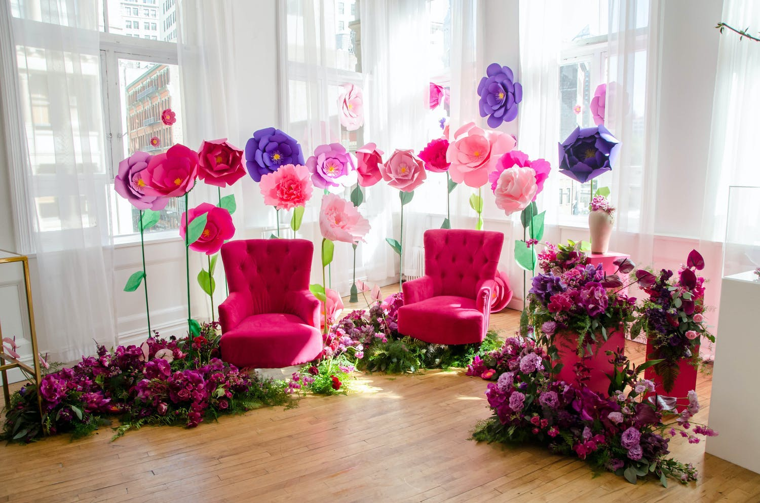 Media event with photo op area featuring two bright pink sofa chairs and giant pink, purple, and red paper flowers | PartySlate