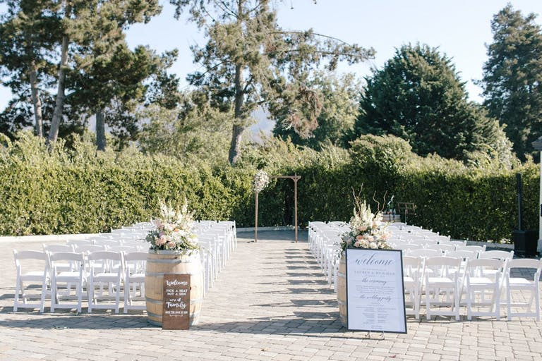 Outdoor wedding ceremony with white chairs and floral-decorated barrels bordered by manicured trees at Folktale Winery & Vineyards in Carmel-by-the-Sea, CA   PartySlate