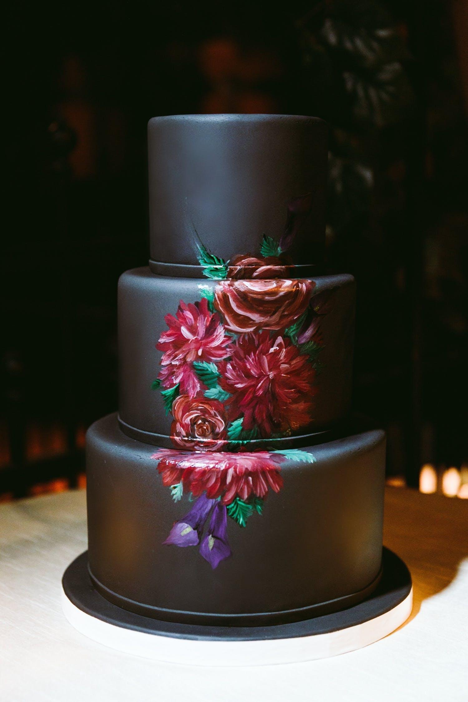 Three-tier black wedding cake with elegant rose design spanning across each tier | PartySlate