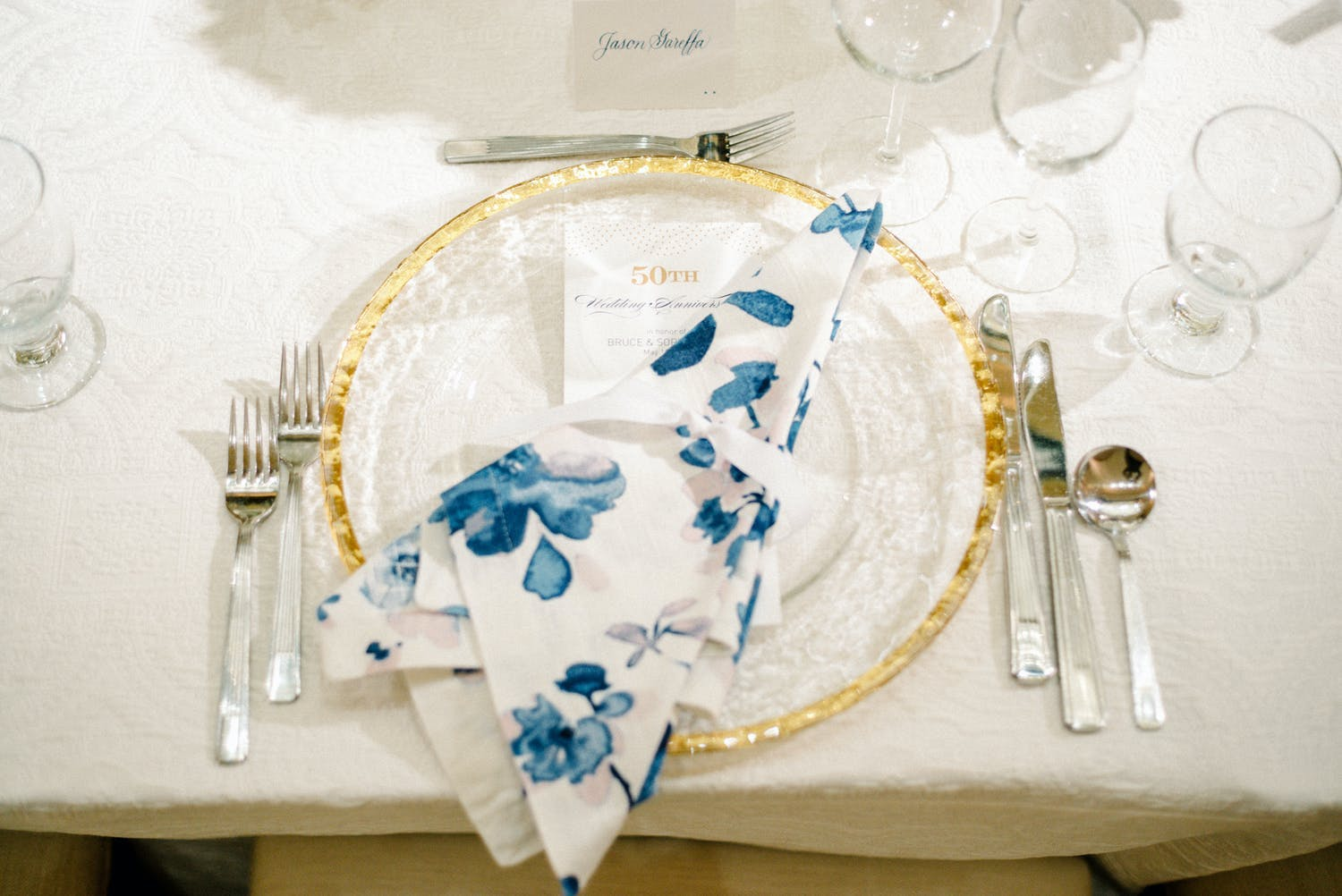 Elegant dinner plate with blue and white floral napkin at 50th-wedding anniversary | PartySlate
