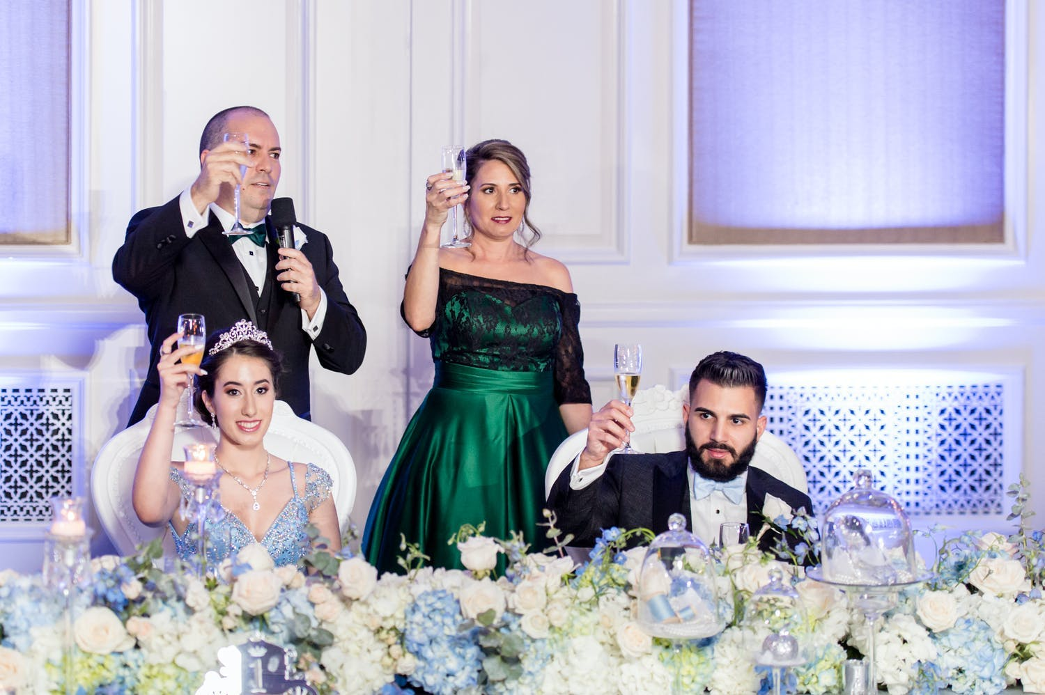 Parents and chambelan escort raise a toast, one of many common quinceañera traditions, for celebrant at fairytale reception | PartySlate