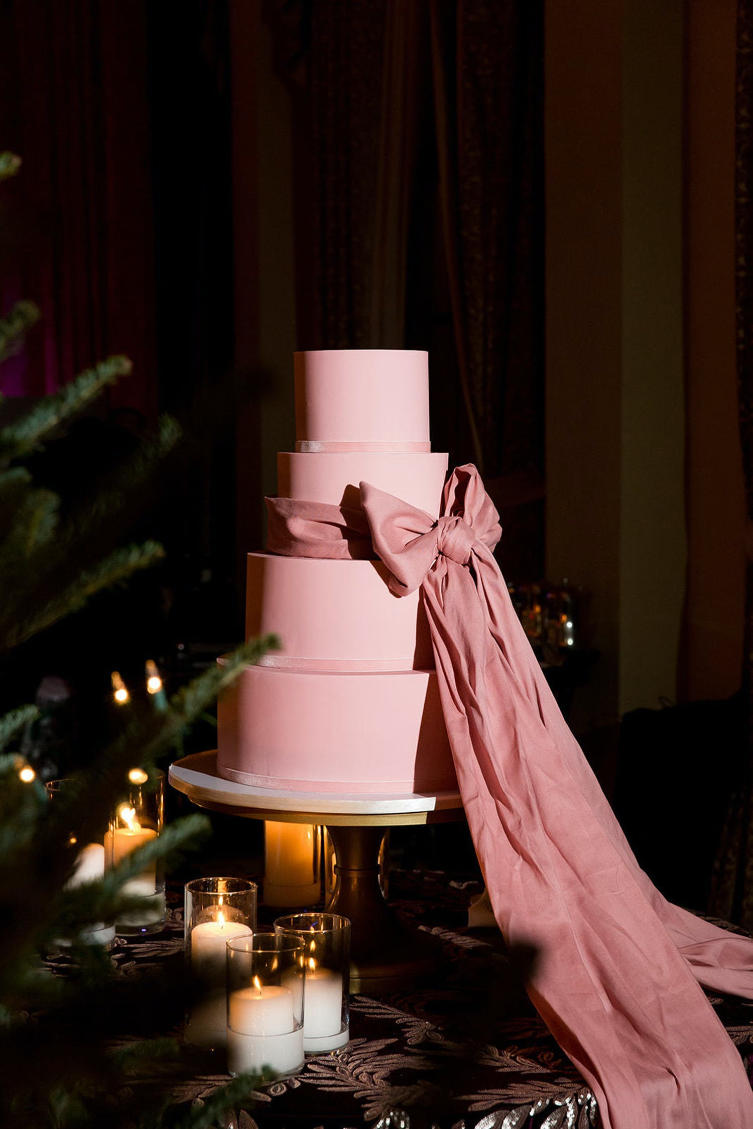 Four tier light pink wedding cake with big pink bow wrapped around it | PartySlate