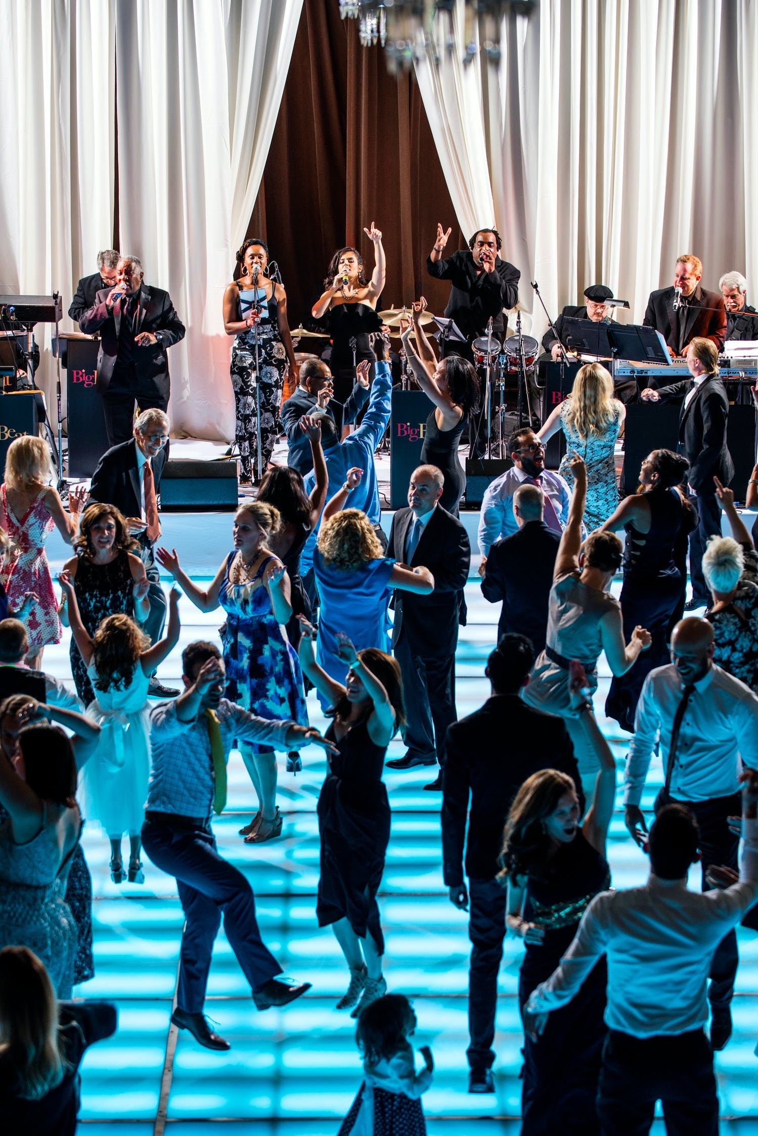 Guests dance on LED blue dance floor at wedding with performance by band Cagen Music LLC of Chicago, IL   PartySlate