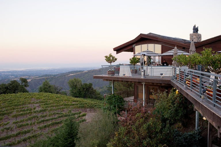 Terrace of a darkwood building at Thomas Fogarty Winery overlooking vineyards and the Santa Cruz Mountains   PartySlate