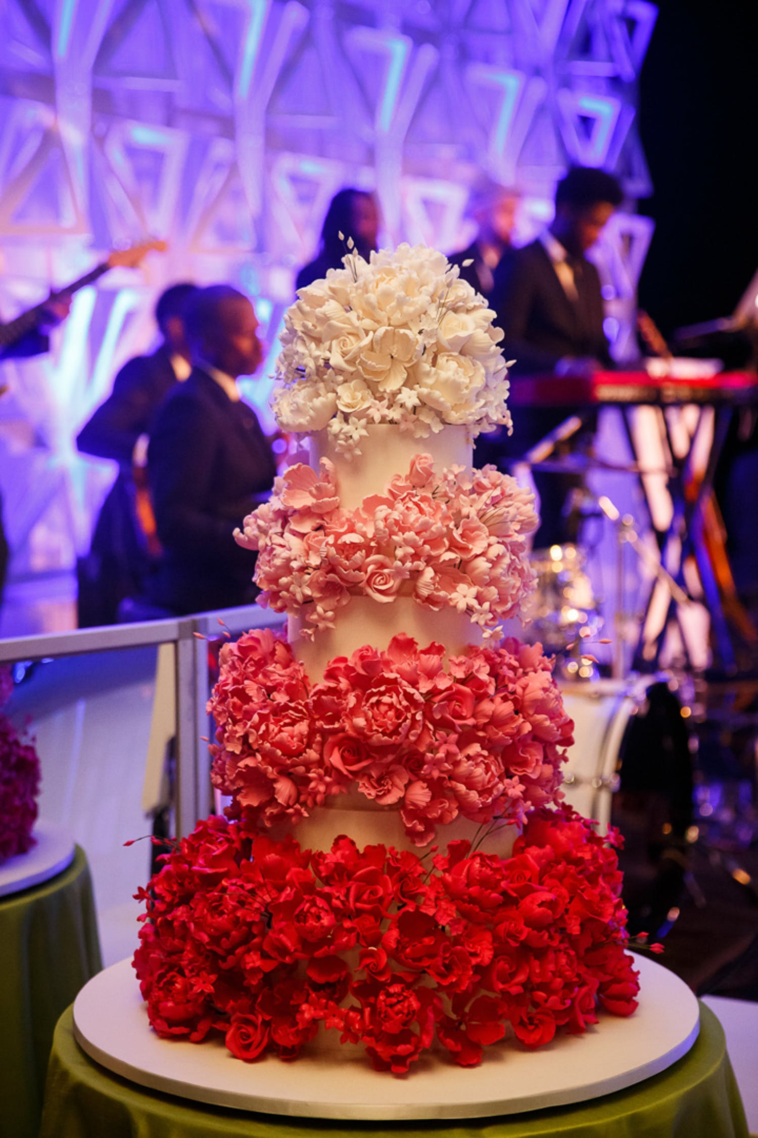 Four-tier cake covered with ombré tiers of flowers going from red to dark pink to pink to white | PartySlate