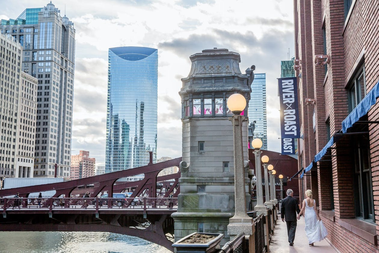 Bride and groom walk down Chicago Riverfront at River Roast Social House for their restaurant wedding Chicago   PartySlate