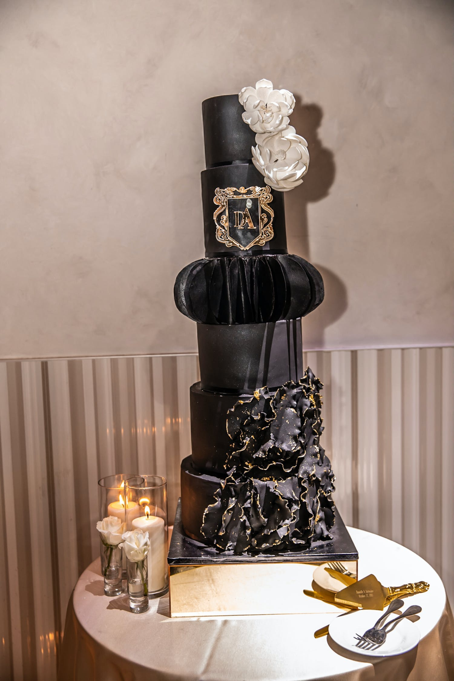 Tall black wedding cake with moody accents and designs | PartySlate