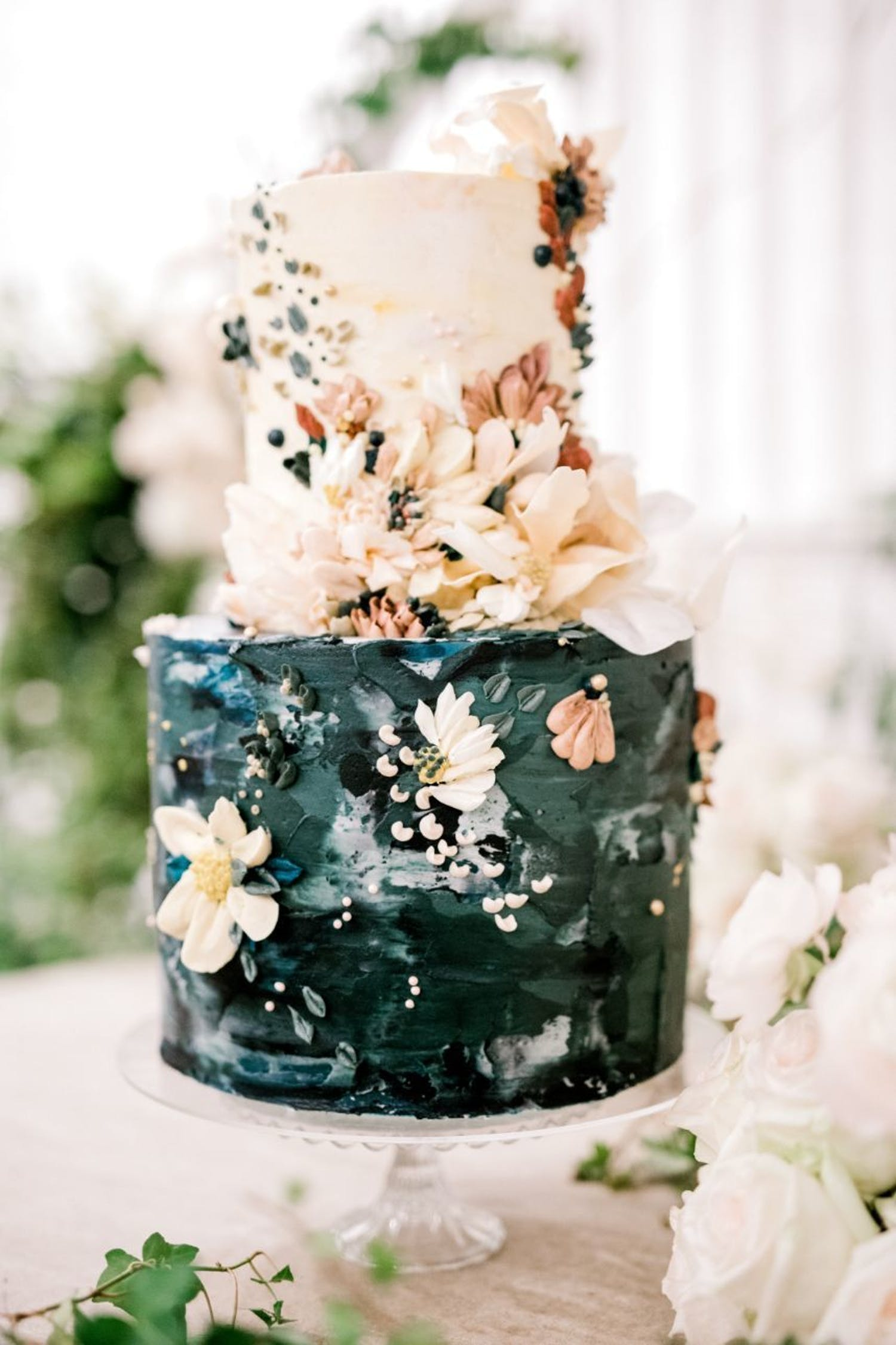 Two-tier wedding cake with green watercolor bottom and cream top with cream-hued flowers | PartySlate