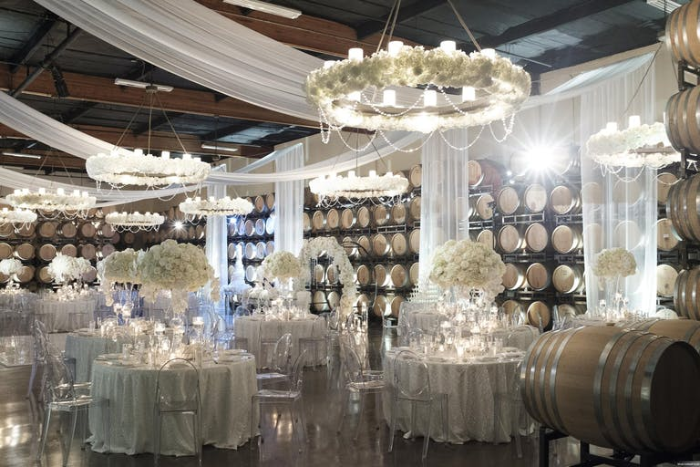 White tablecloths, floral centerpieces, and draping tapestries at white themed wedding in Callaway Vineyard and Winery's barrel room   PartySlate