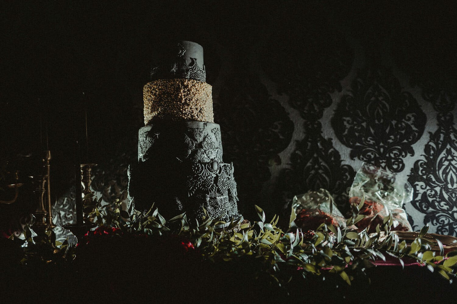 Moody black wedding cake with multiple textures and one tan tier | PartySlate