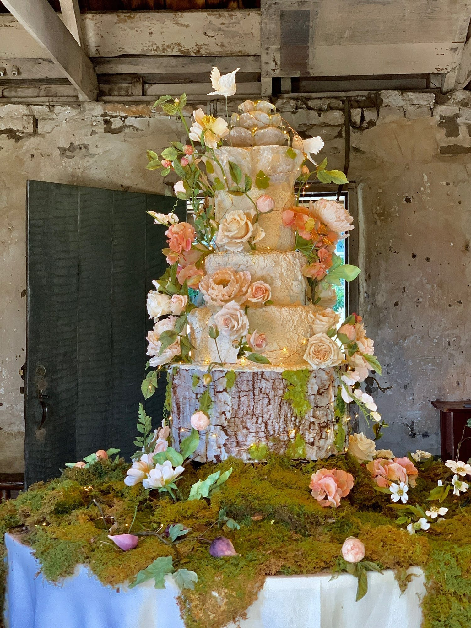 Large wedding cake on tree-trunk base and bed of moss with tiers covered in nature-like floral designs | PartySlate
