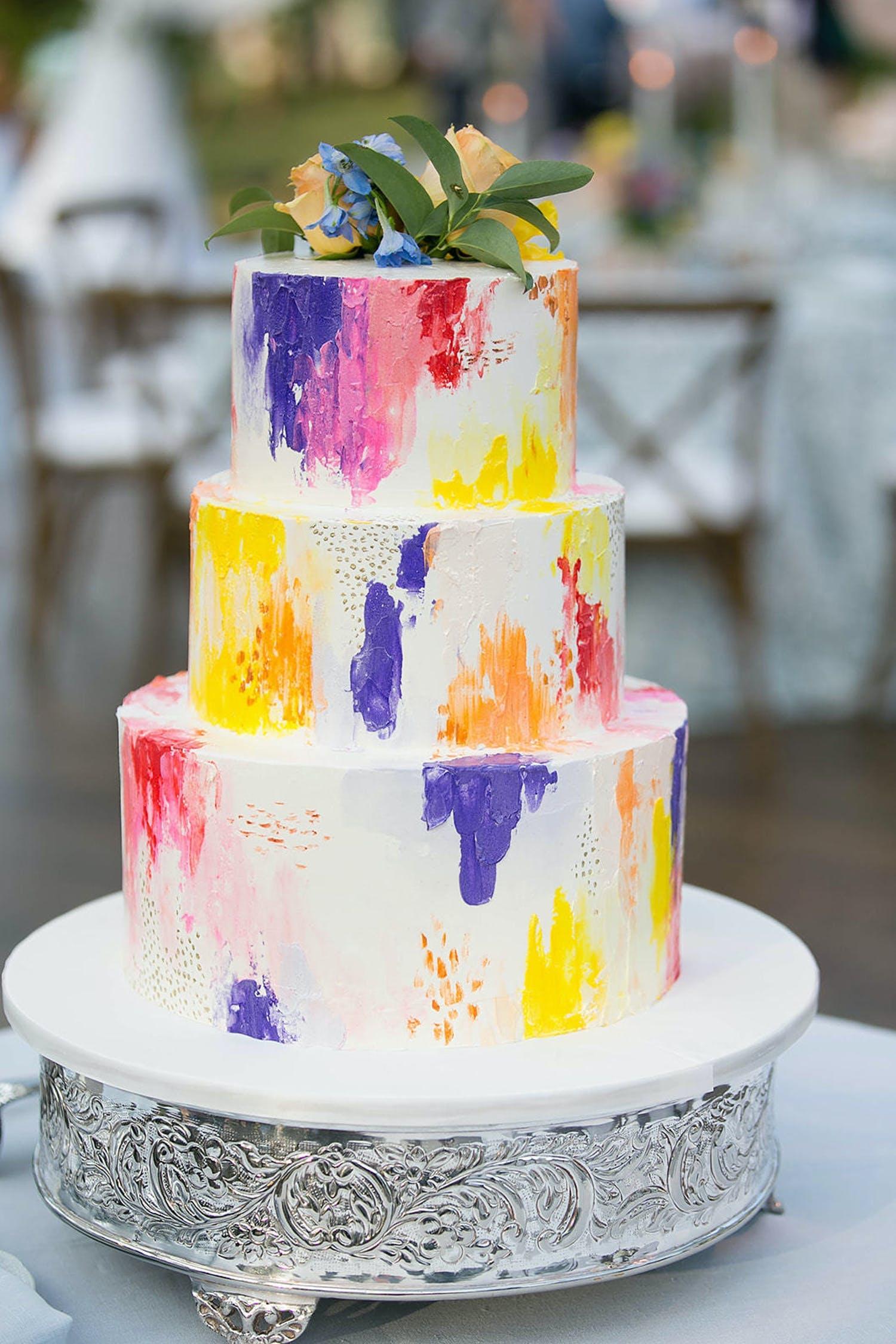 Three-tier white wedding cake with splatter of pink, purple, orange and yellow | PartySlate