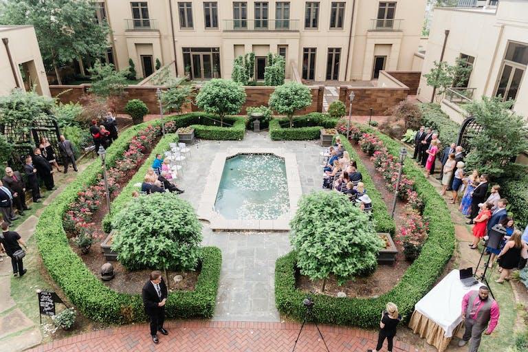 Outdoor Wedding Ceremony Set in Manicured Courtyard with Pool Focal Point at Waldorf Astoria Atlanta Buckhead in Atlanta, GA   PartySlate