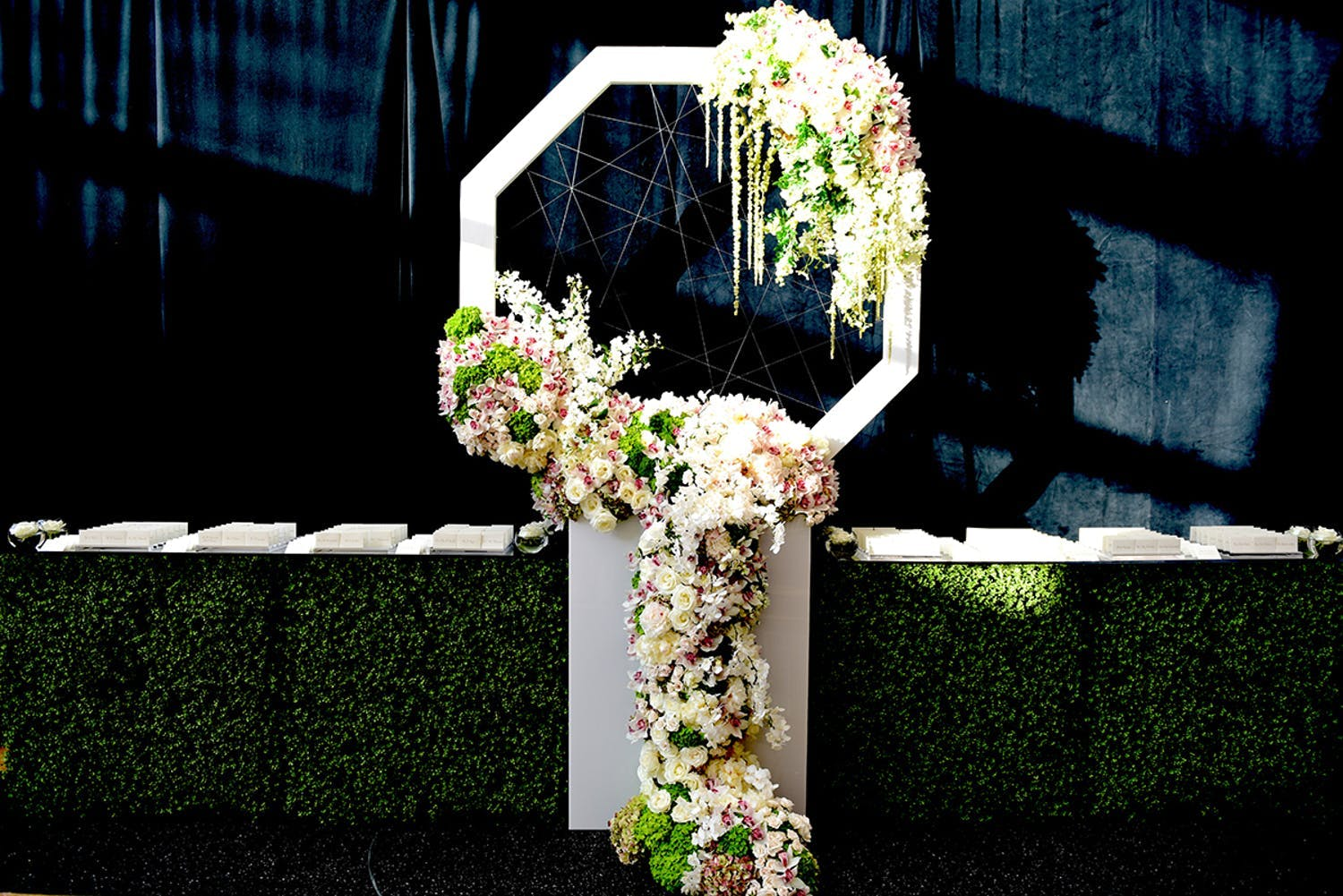Wedding seating charts on table with boxwood paneling and giant white hexagonal dream catcher | PartySlate