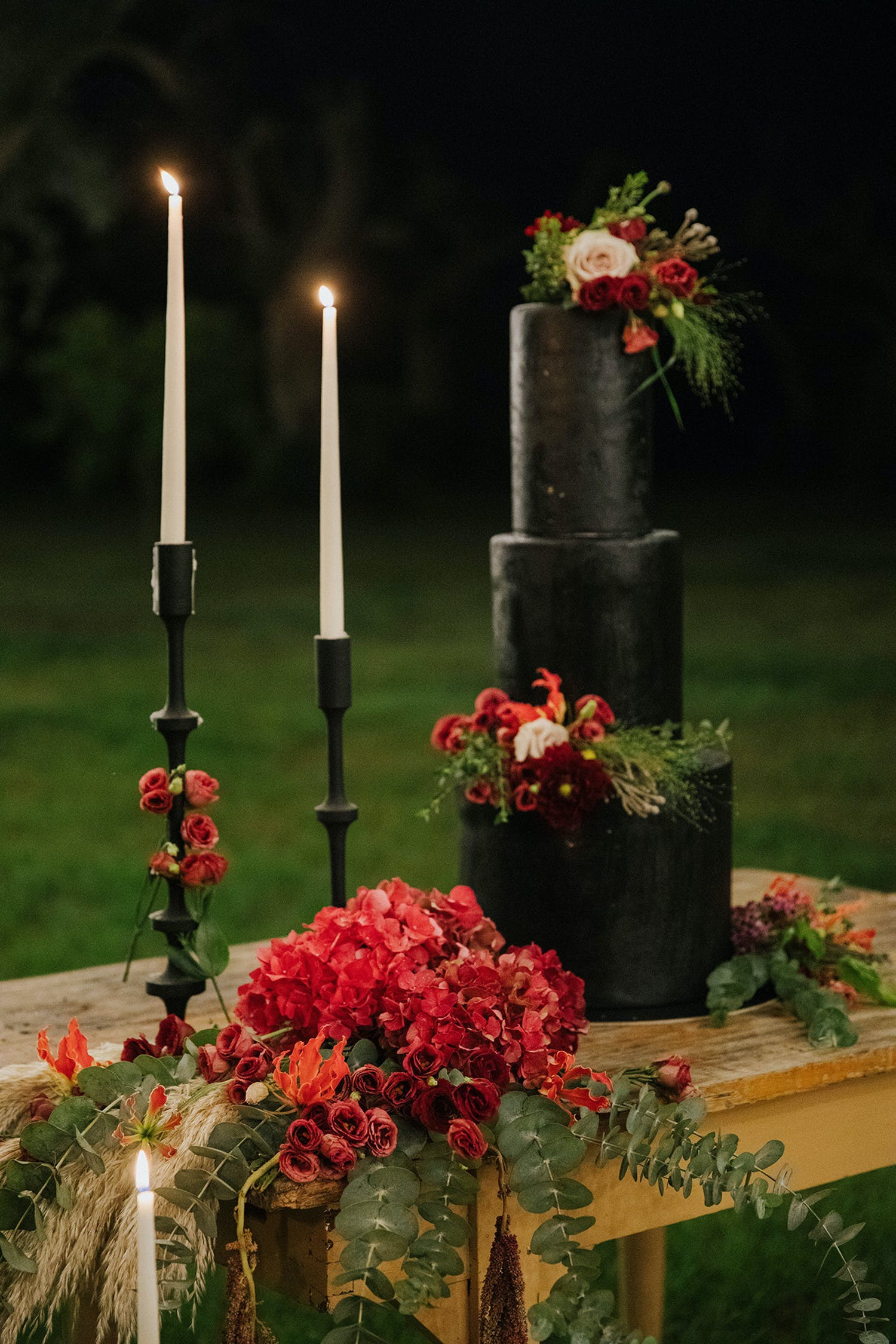Three tier skinny black wedding cake with two red flowers | PartySlate
