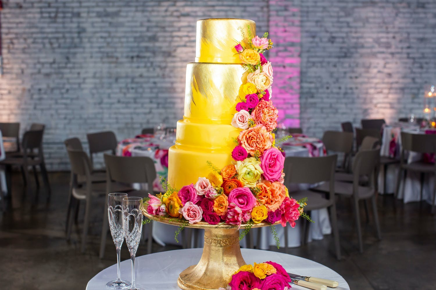 Gold Wedding Cake With Bright and Colorful Flowers | PartySlate