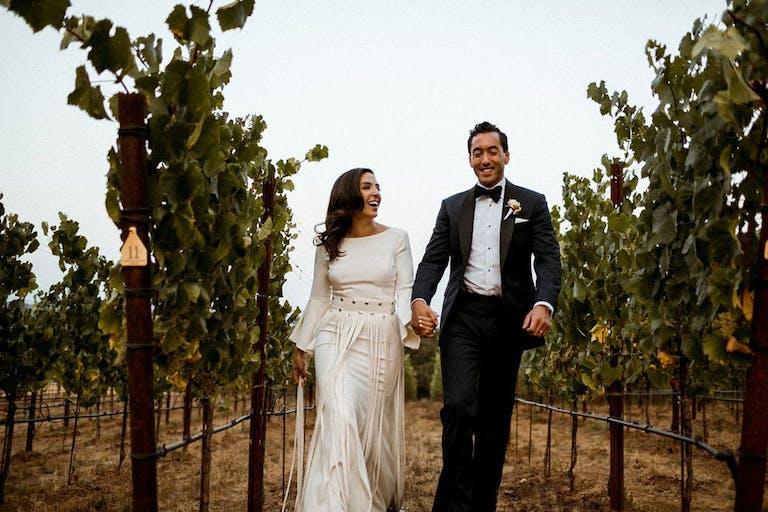 Bride and Groom walk through vineyards at Arista Winery in Healdsburg, CA   PartySlate