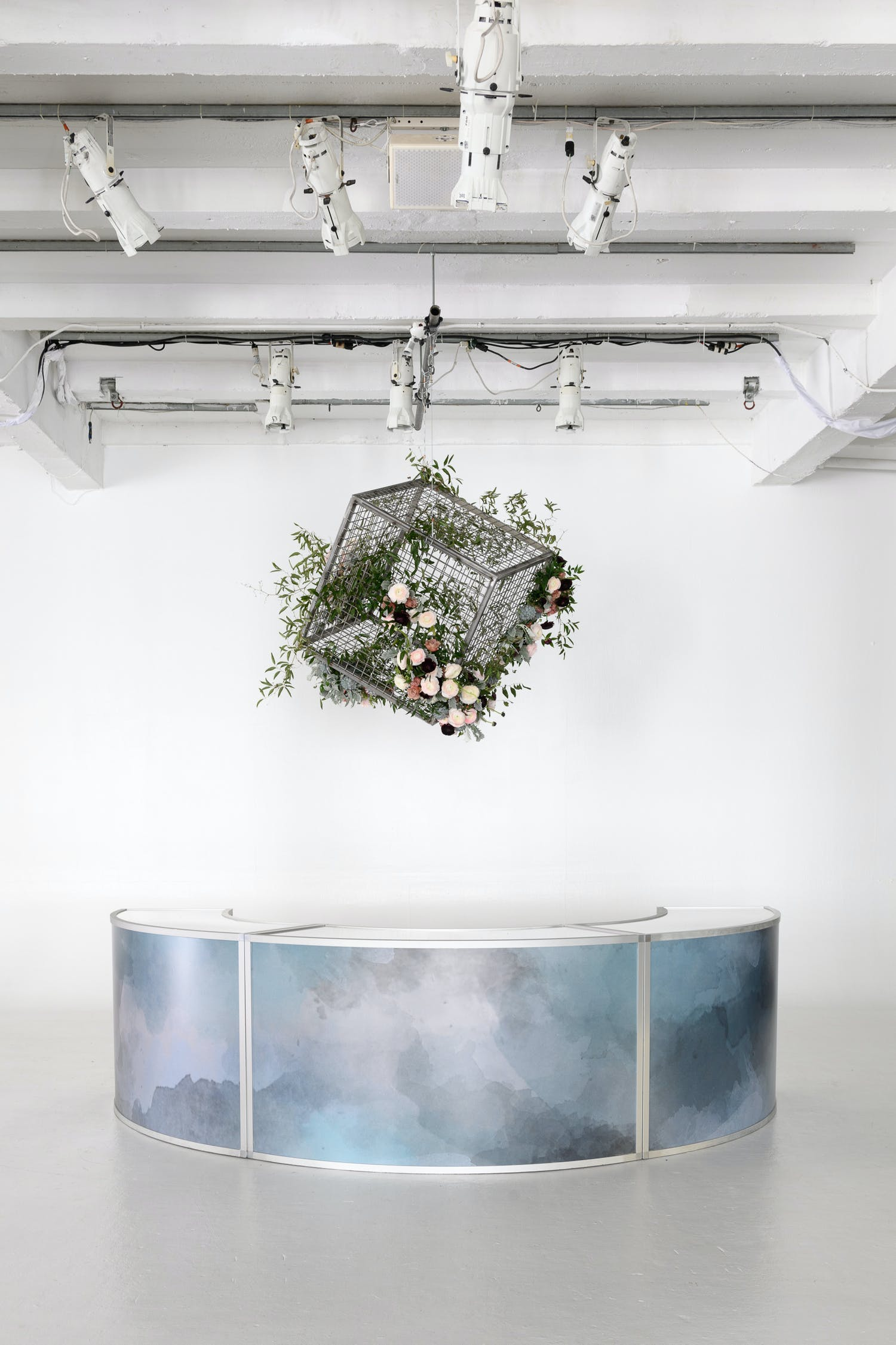 A white raw space with a galaxy patterned reception table against a white wall.. A black cube cage hangs above with greenery and pink florals | PartySlate