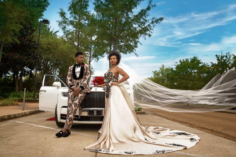 Bride and Groom in Unique Clothing Pose in Front of Vintage White Car at Wedding Planned by Wise Events & Design of Houston, TX   PartySlate