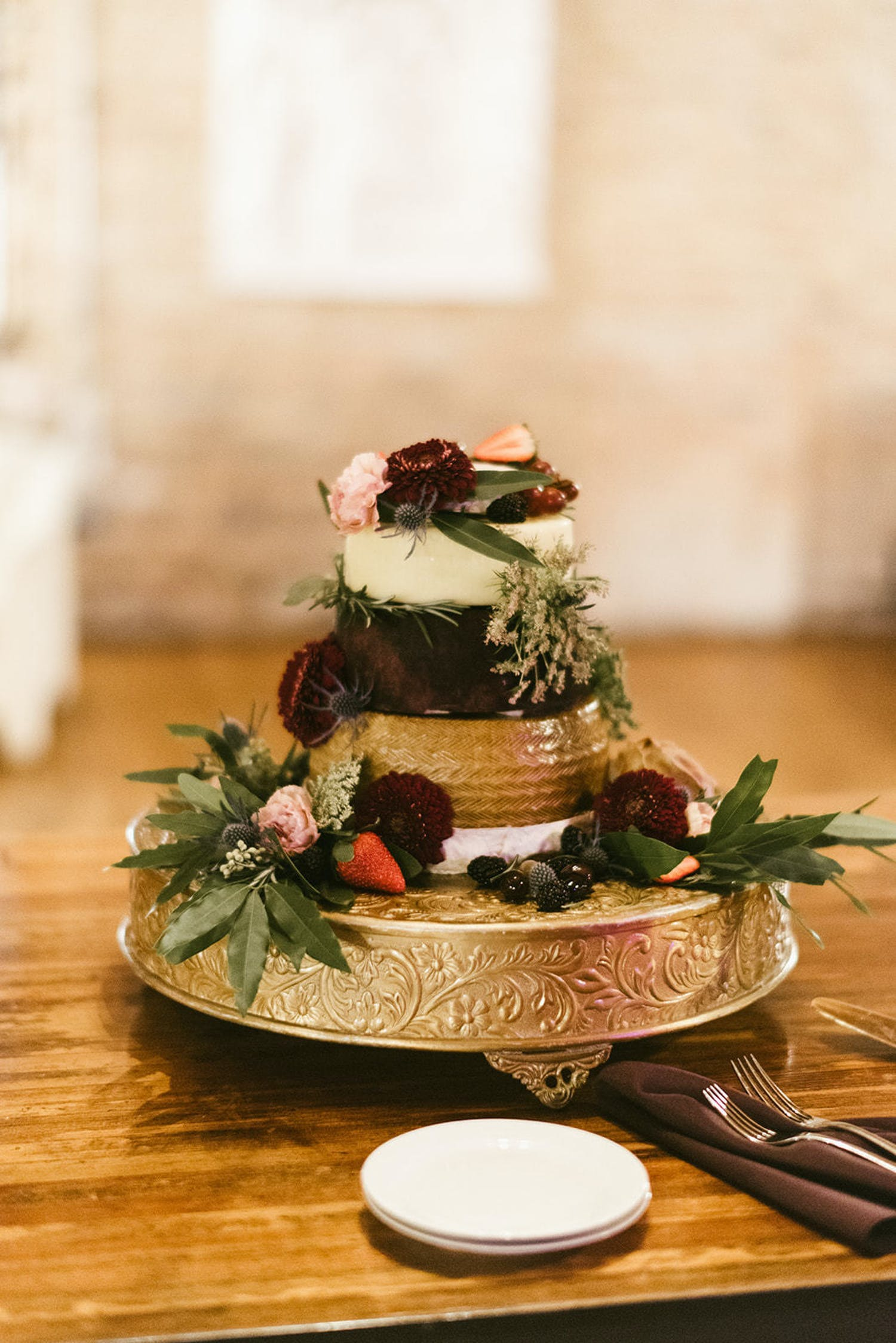 Small multi-tiered gold accented wedding cake with multiple flavors | PartySlate