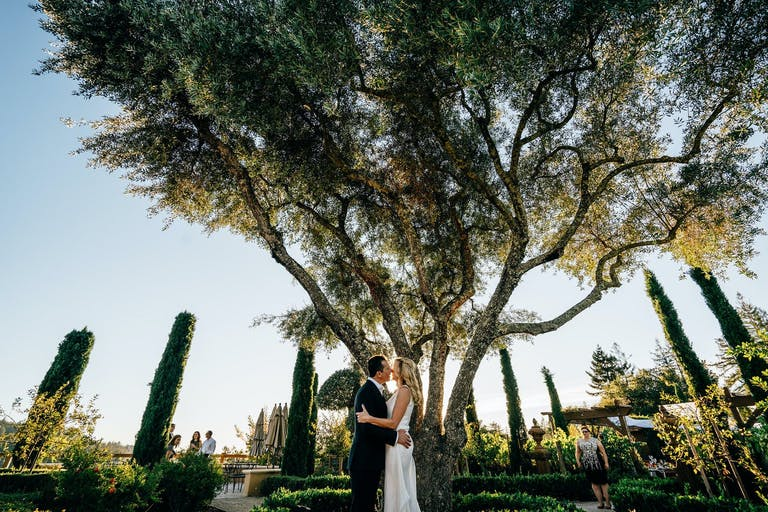 Bride and groom share a kiss in beautifully manicured garden at Regale Winery and Vineyards   PartySlate