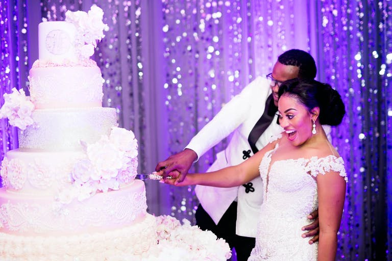 Bride and Groom Cut into Towering White Wedding Cake Against a Glittery Purple Backdrop   PartySlate