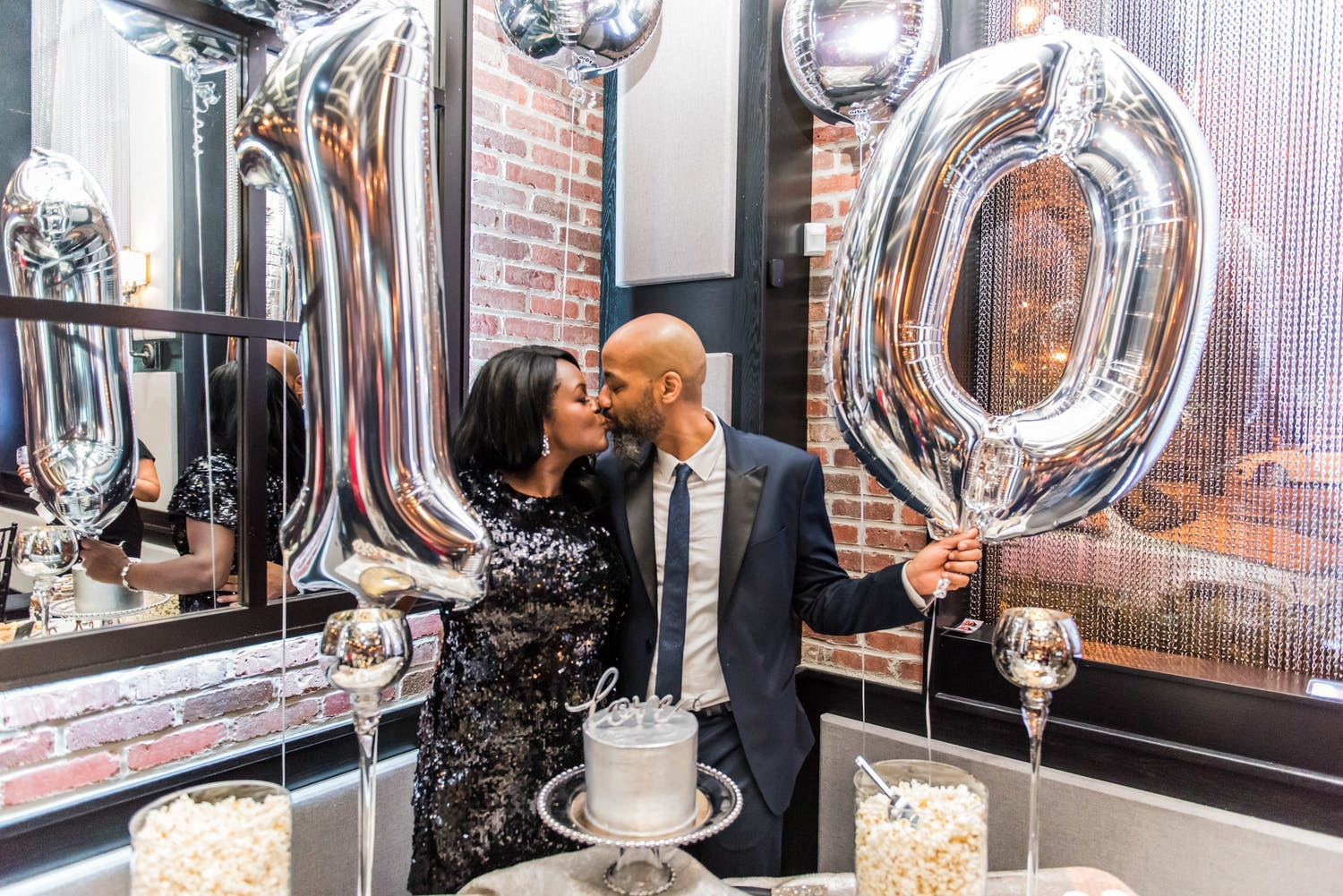 Couple kiss while holding silver balloons that spell out 10 for 10th-wedding anniversary party | PartySlate