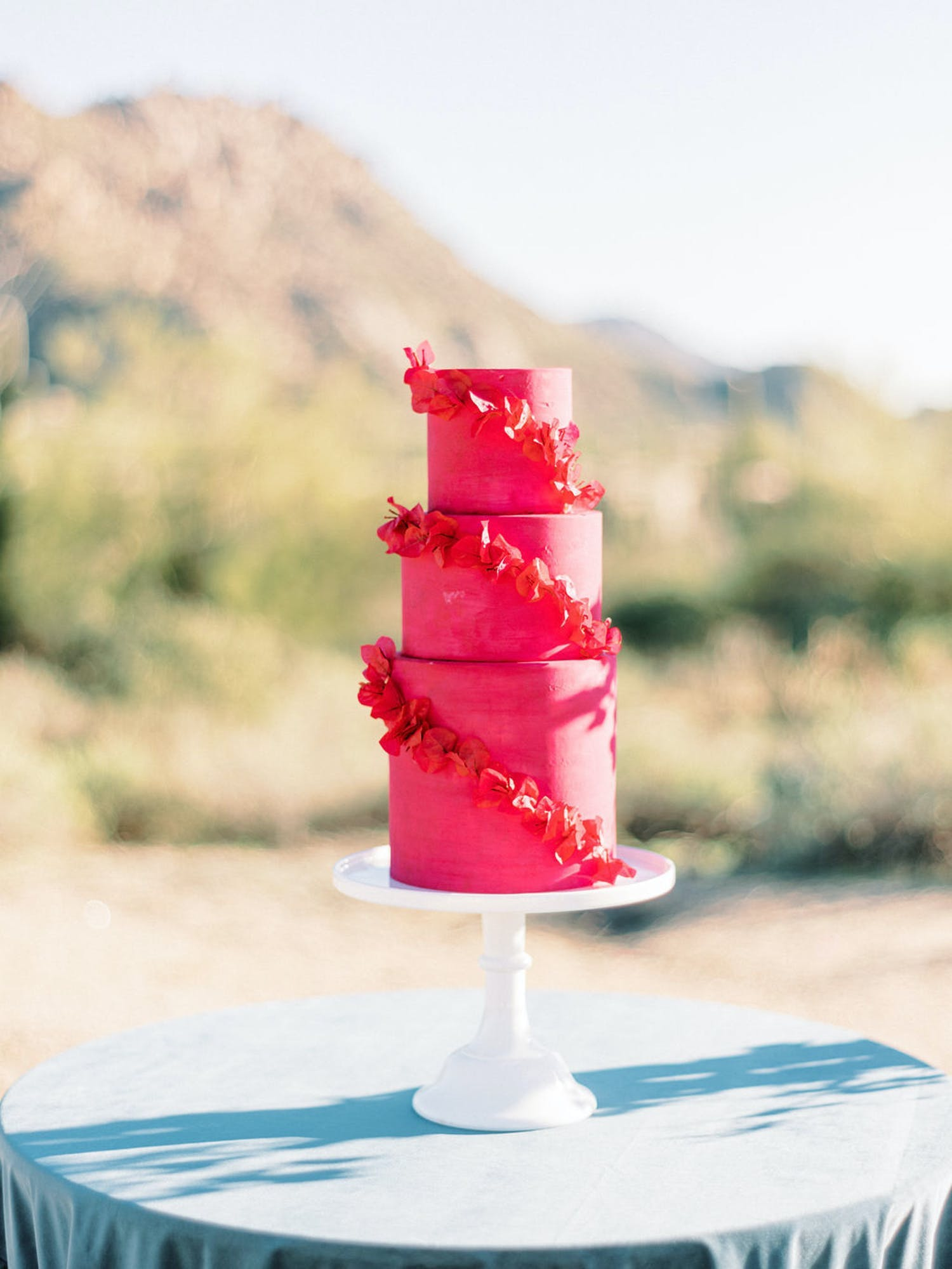 Three-Tiered Hot Pink Wedding Cake With Red Orchids Wrapped Around It | PartySlate