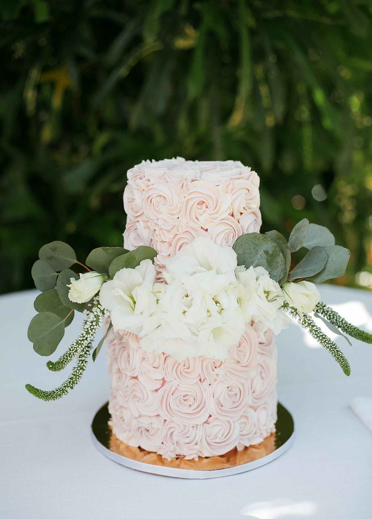 Pink buttercream cake with plush white florals and eucalyptus leaves between two tiers | PartySlate