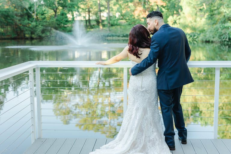 Groom kisses bride's head as she looks at pond at Forever 5 Events in Conroe, TX   PartySlate