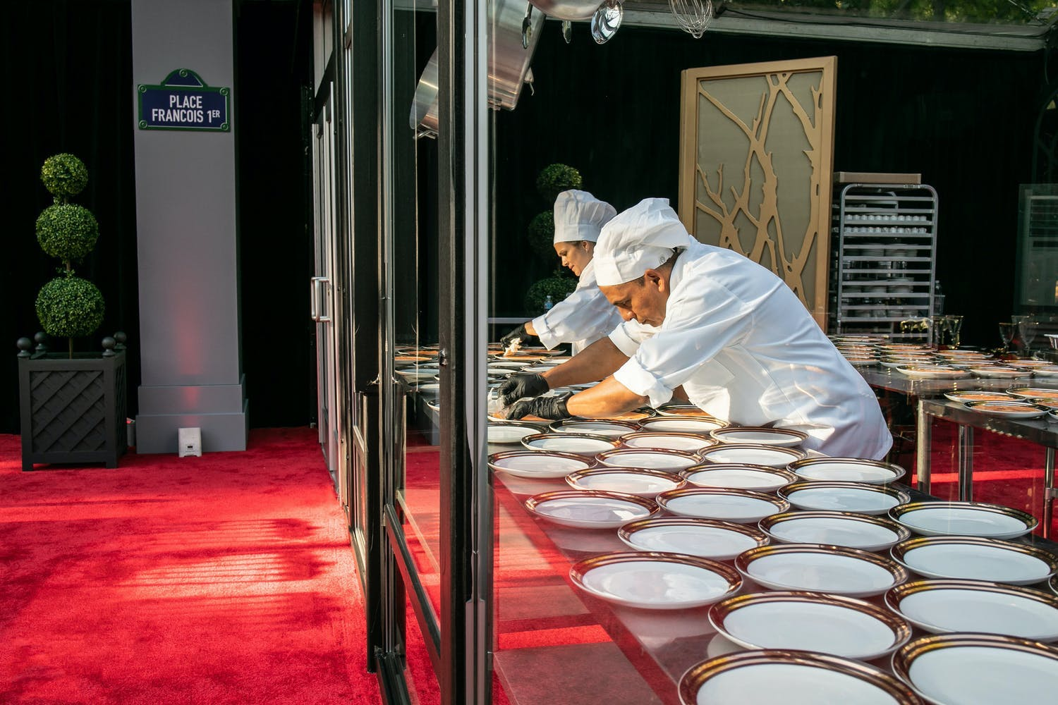 Glass panel that allows guests to see chefs preparing food for 50th anniversary party | PartySlate