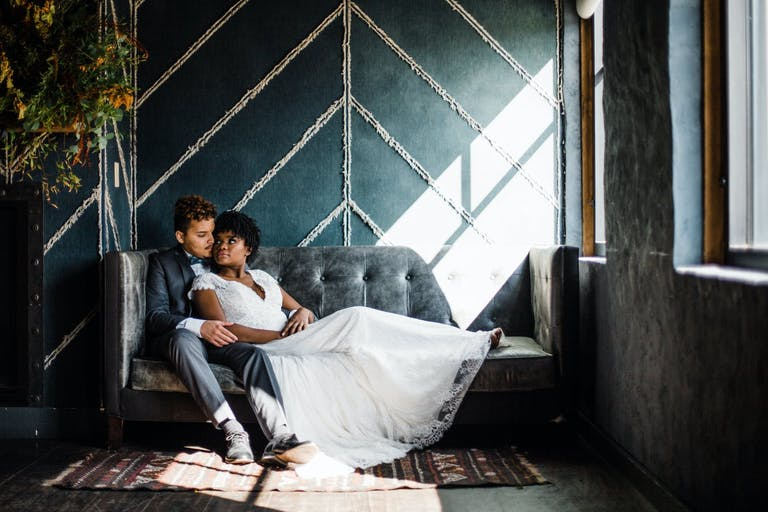 Bride and groom rest on sofa against chevron-denim wall backdrop at The Dawson in Chicago, IL   PartySlate