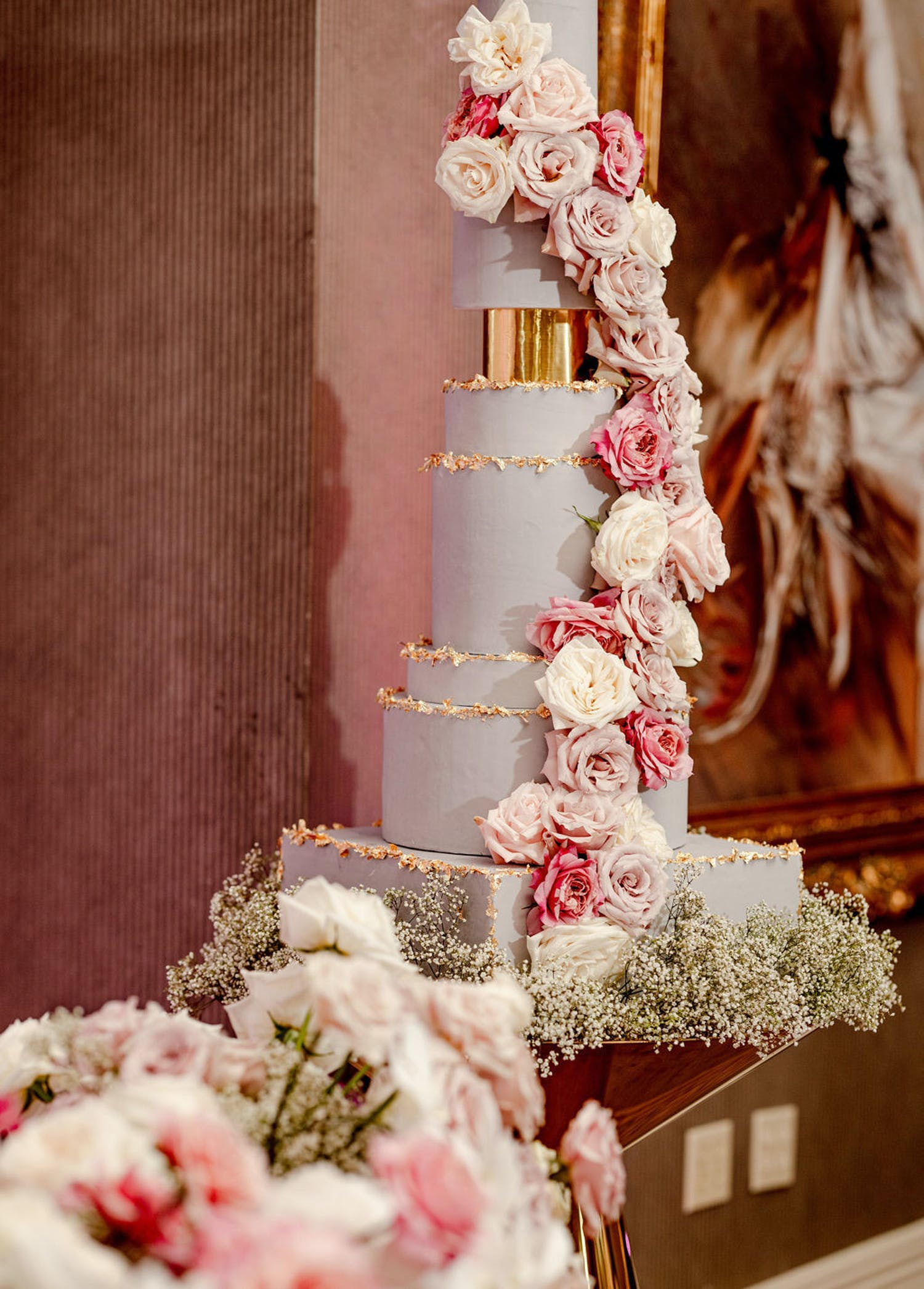 Towering White and Gold Wedding Cake With Cascade of Pink Roses and Bed of Baby's Breath Designed by Déjà vu Sweets | PartySlate