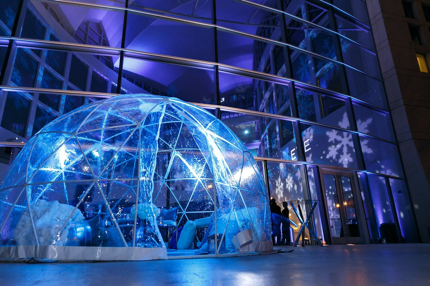 Transparent glamping igloo is lit up by blue lights in front of a wall of windows at winter blue corporate event party | PartySlate