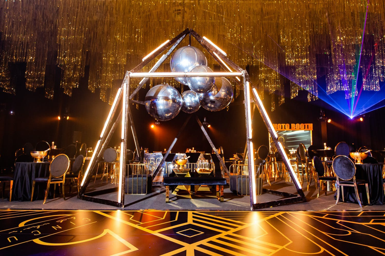 Golden pillar lights create a dome-like structure over a seating area at 50th-birthday party | PartySlate