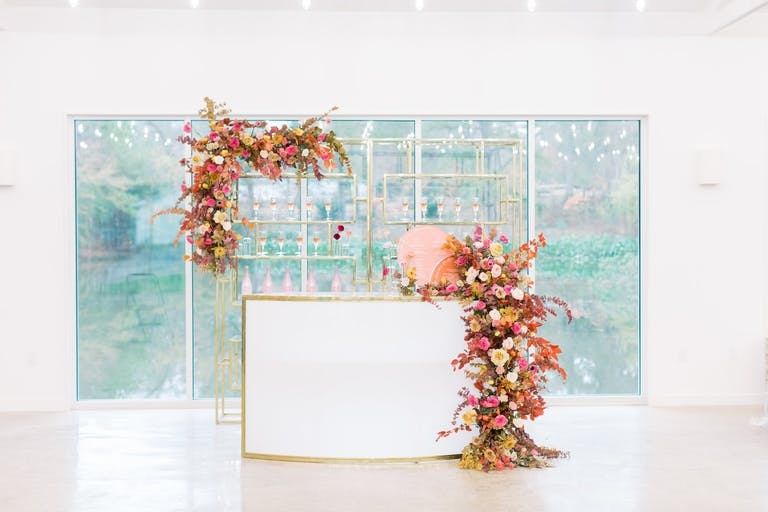 Mod and Glam White Party Bar Area with Cascading Warm-Hued Florals   PartySlate