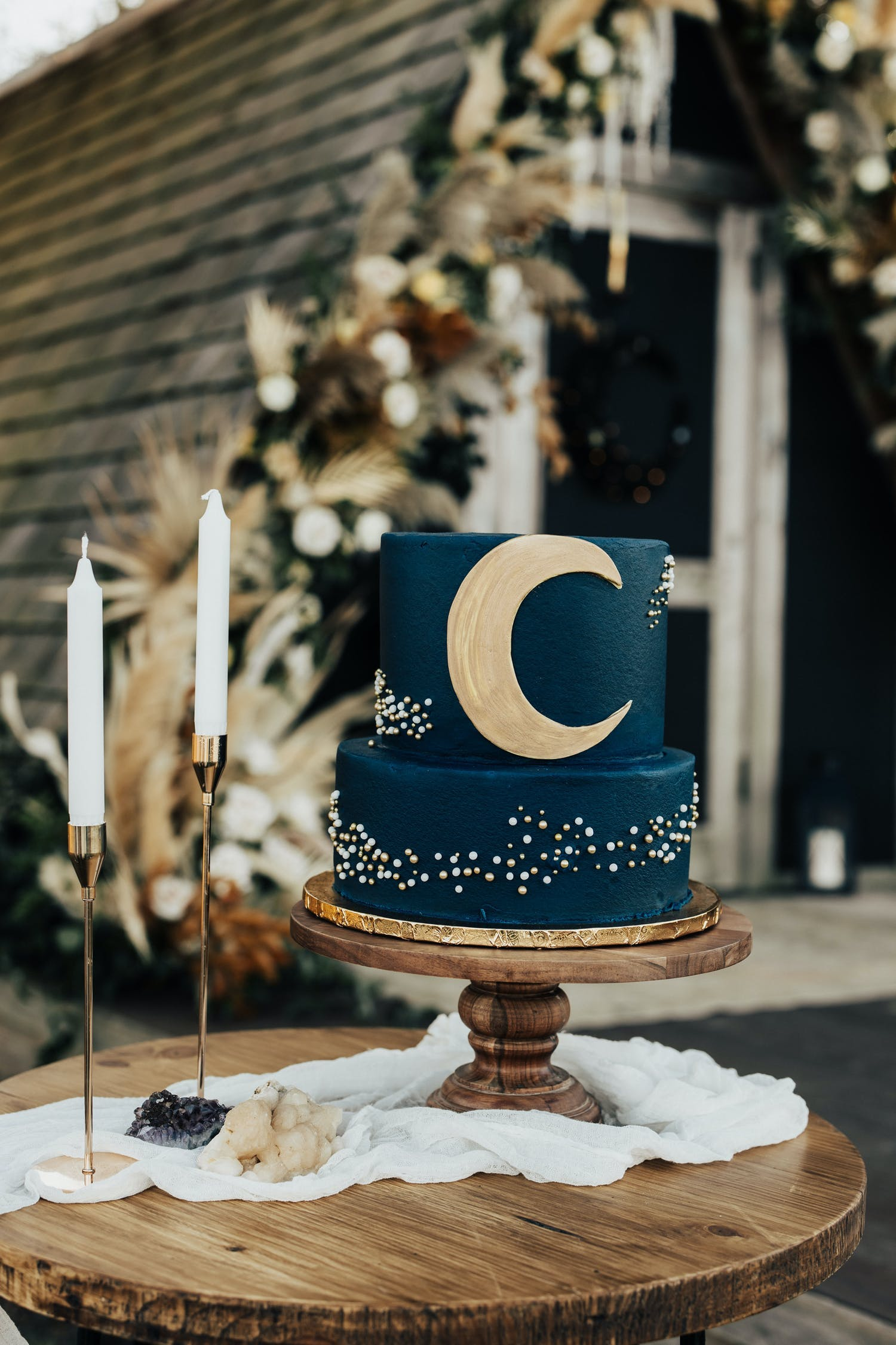 Two-tier navy blue wedding cake with crescent moon design on top tier | PartySlate