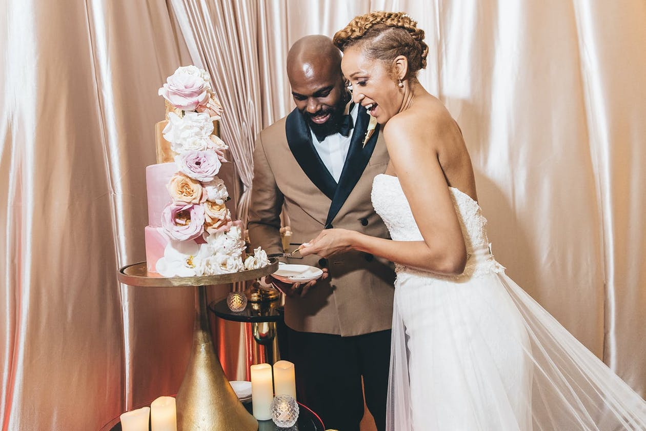 Bride and Groom Cut Into Pink Cake With White Florals, One of Many Unique Wedding Cake Ideas | PartySlate
