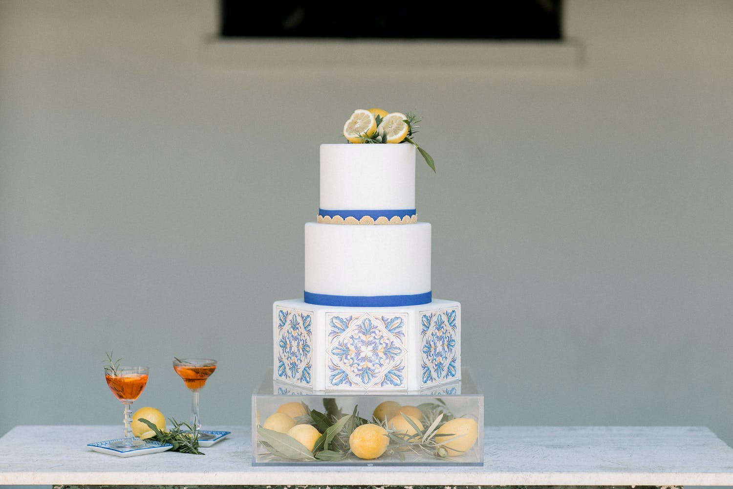 Three-tier wedding cake with a hexagon bottom tier and blue and white design on a lucite cake stand filled with lemons | PartySlate