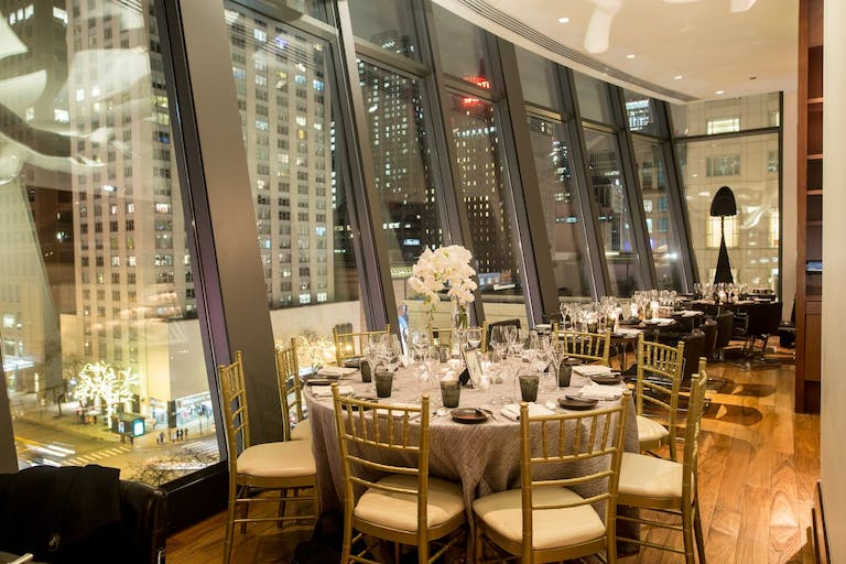 Wedding reception at NoMI Kitchen with floor-to-ceiling cantilevered windows that show off both downtown Chicago and Lake Michigan   PartySlate