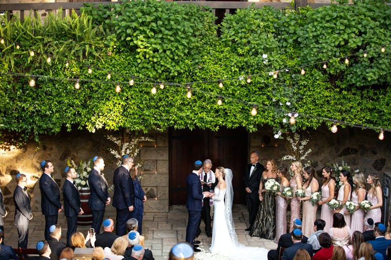 Bride and groom under a vibrant green wall altar at V Sattui Winery, a Napa winery estate   PartySlate
