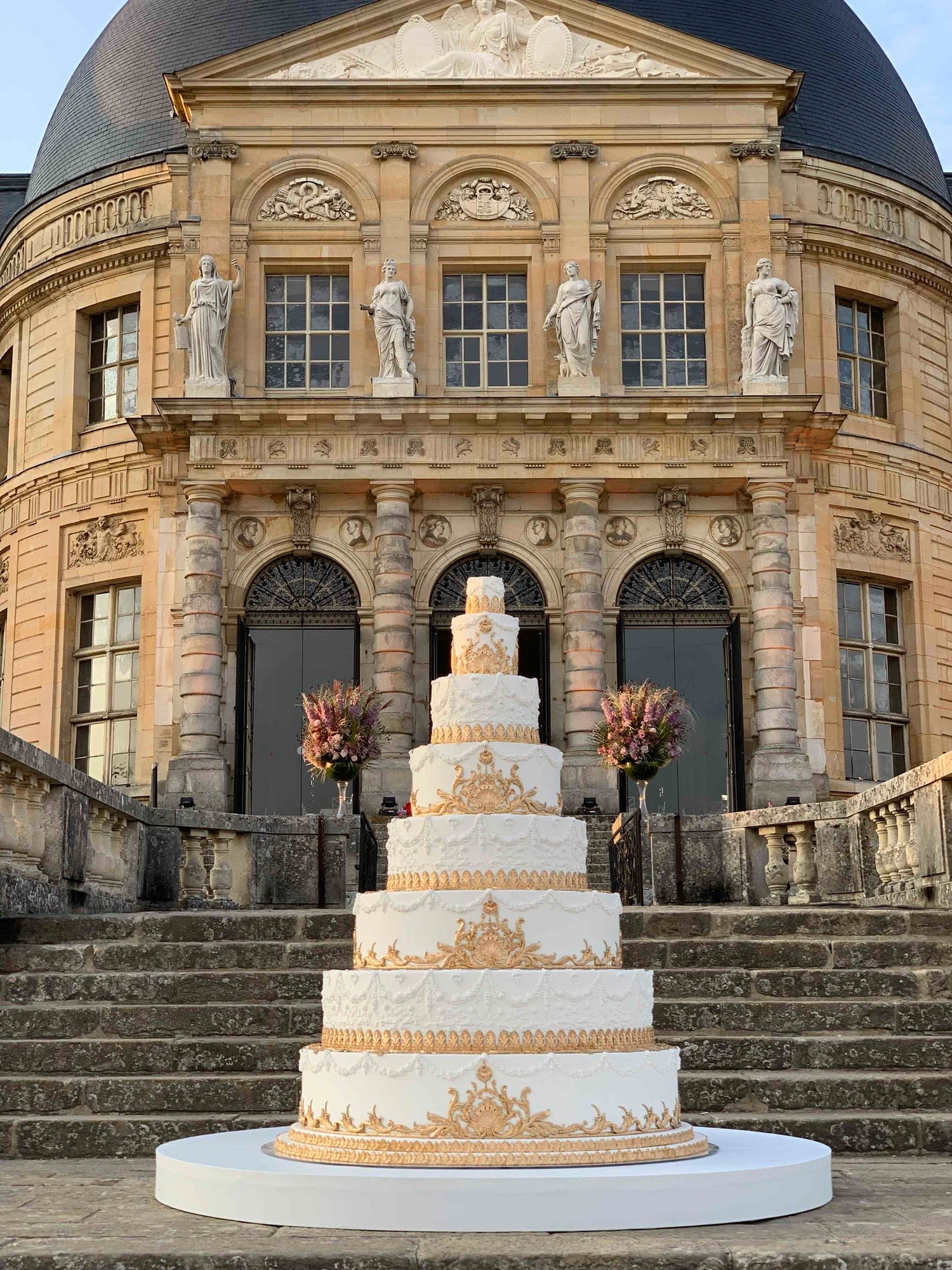 Towering eight tier white wedding cake with ornate gold icing designs | PartySlate