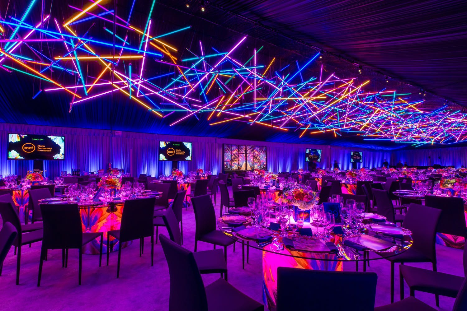 Geometric blue, orange, and pink neon lights ceiling installation at electric gala | PartySlate