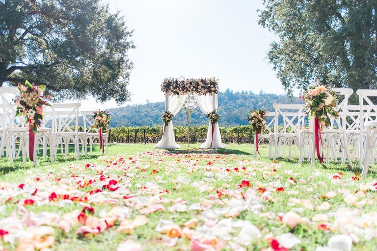 Wedding aisle blanketed in bright pink petals and floral arrangements on white ceremony chairs at Charles Krug Winery in St Helena, CA   PartySlate