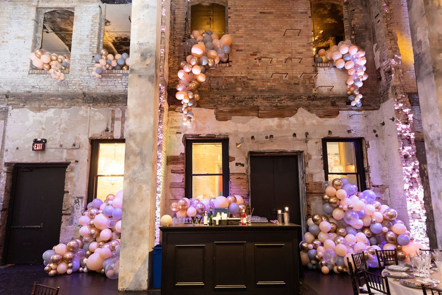 Raw Venue Space with Brick Soaring Walls Covered in Cascading Purple and Pink Balloons for 50th-Wedding Anniversary Party | PartySlate