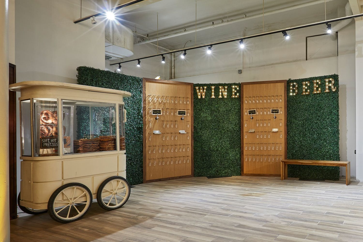 Self-serve wine and beer wall with boxwood backdrop | PartySlate