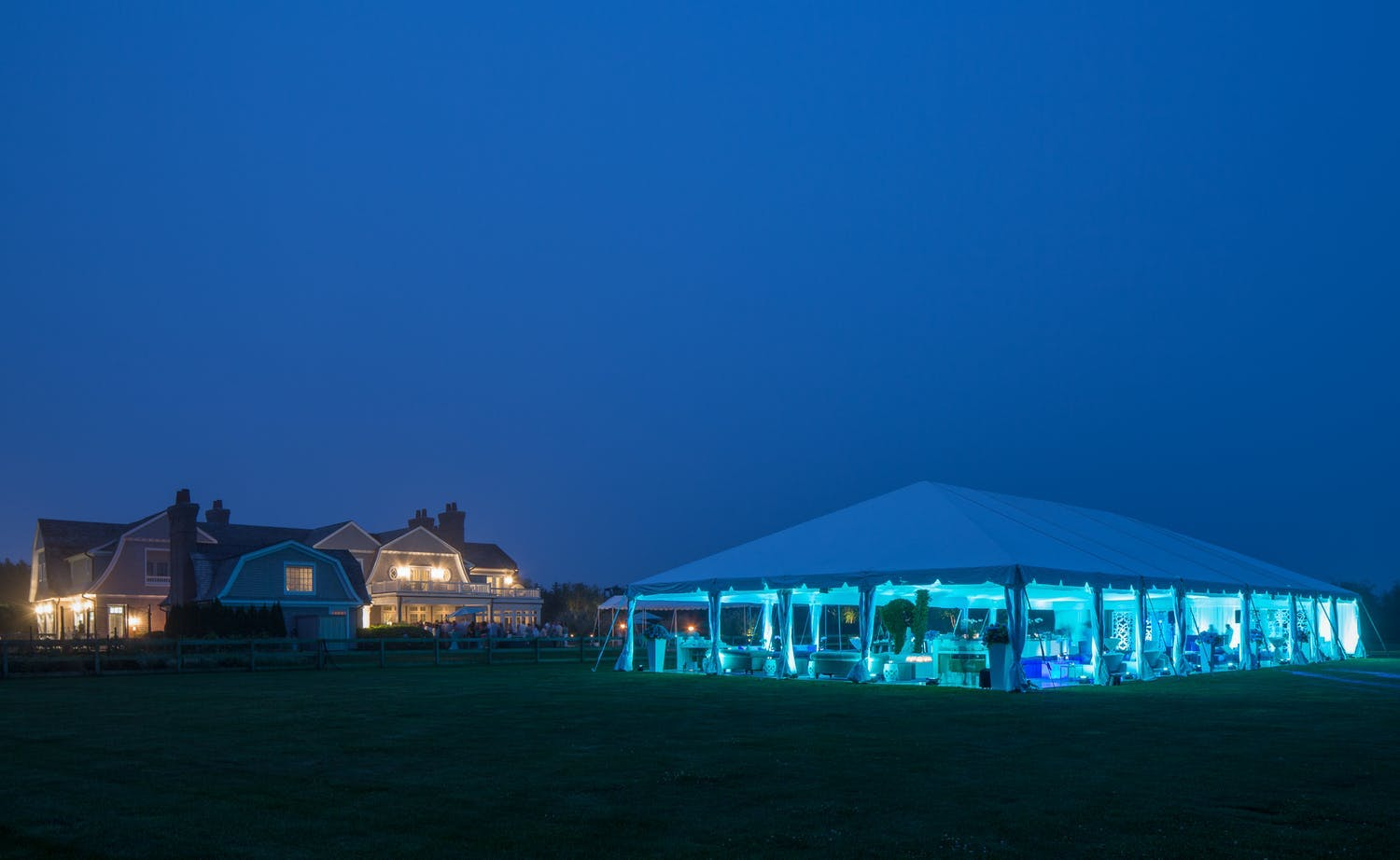 Tented 30th-wedding anniversary with blue uplighting at night | PartySlate